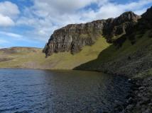 Below dark crags